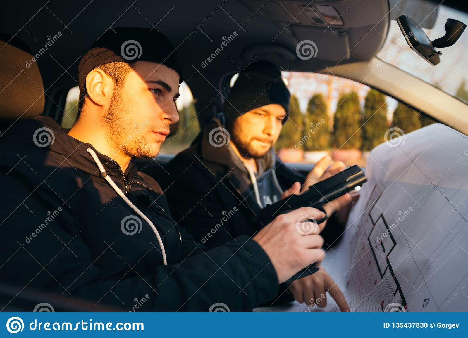Two Robbers Planning And Pointing On The Blueprint Map Their Objective While Holding Their Guns