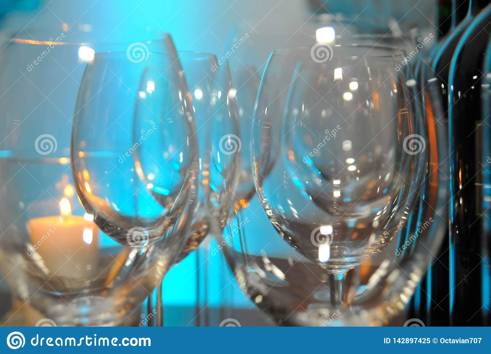 Two rows of empty glasses on a table