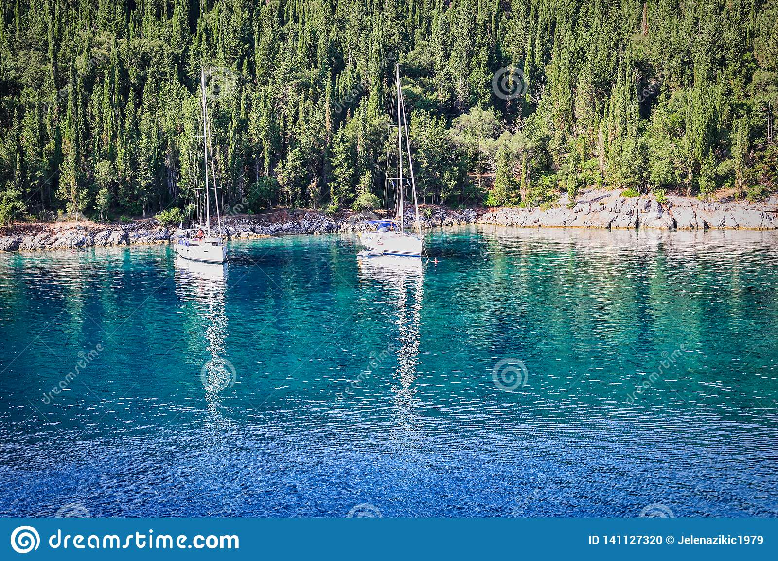Two sailboats anchored in an emerald bay