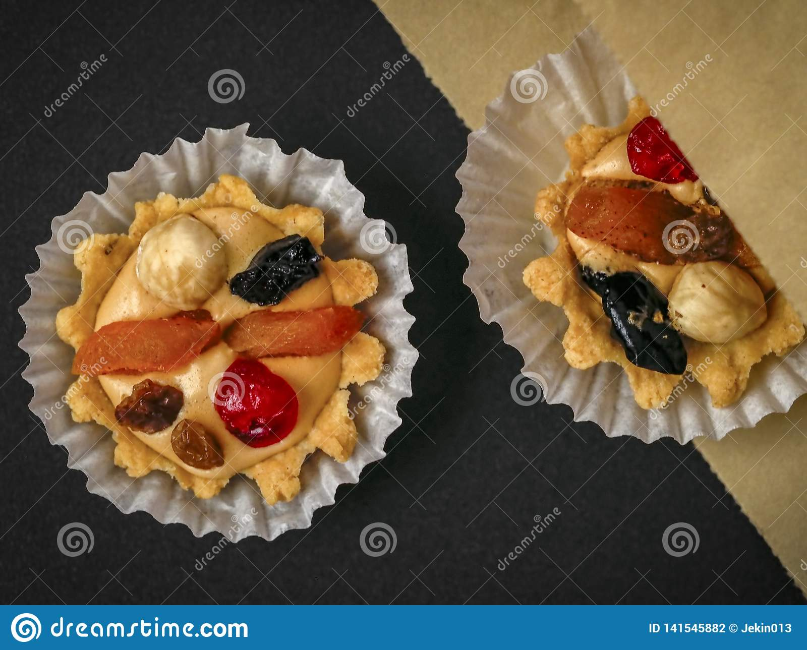 Two sand air cream, berries and nuts cakes