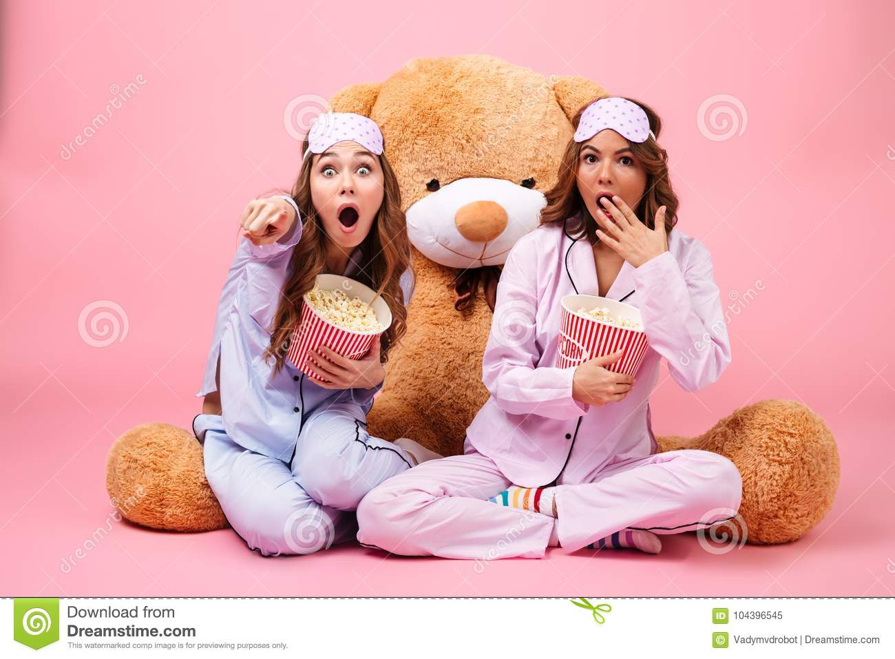 Two scared pretty girls dressed in pajamas pointing finger at camera while  sitting with a big teddy bear and eating popcorn isolated over pink  background 5aad9283a