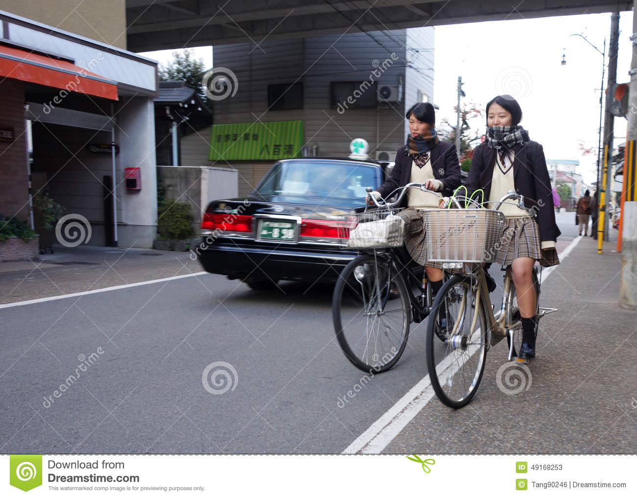Two School Girls Are Cycling In The Road In Kyoto, Japan