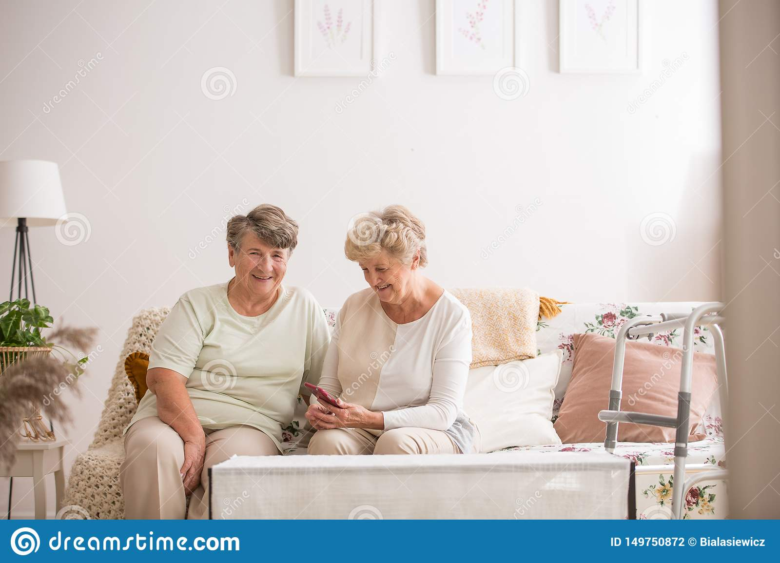 Two senior friends sitting together at couch