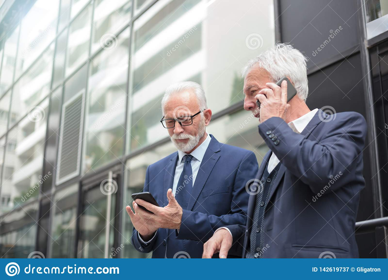Two happy senior businessmen using smart phones, talking and messaging