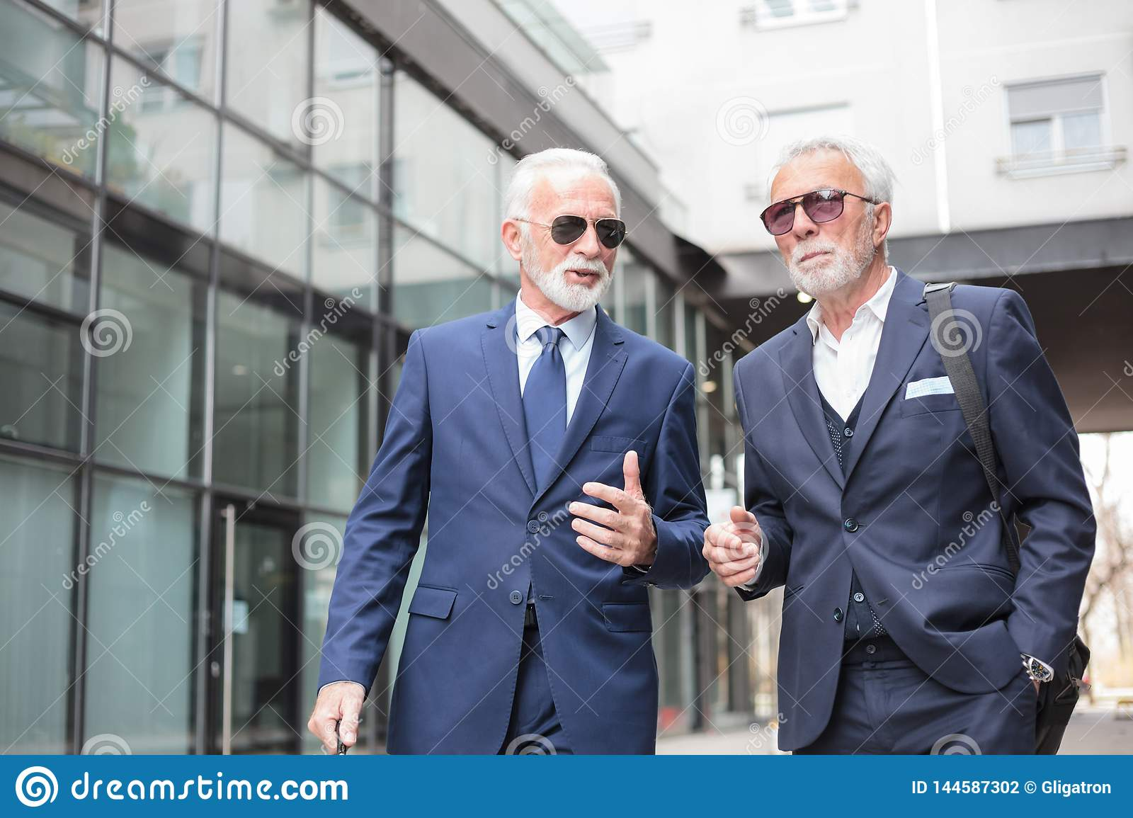Two senior businessmen walking down the street, discussing
