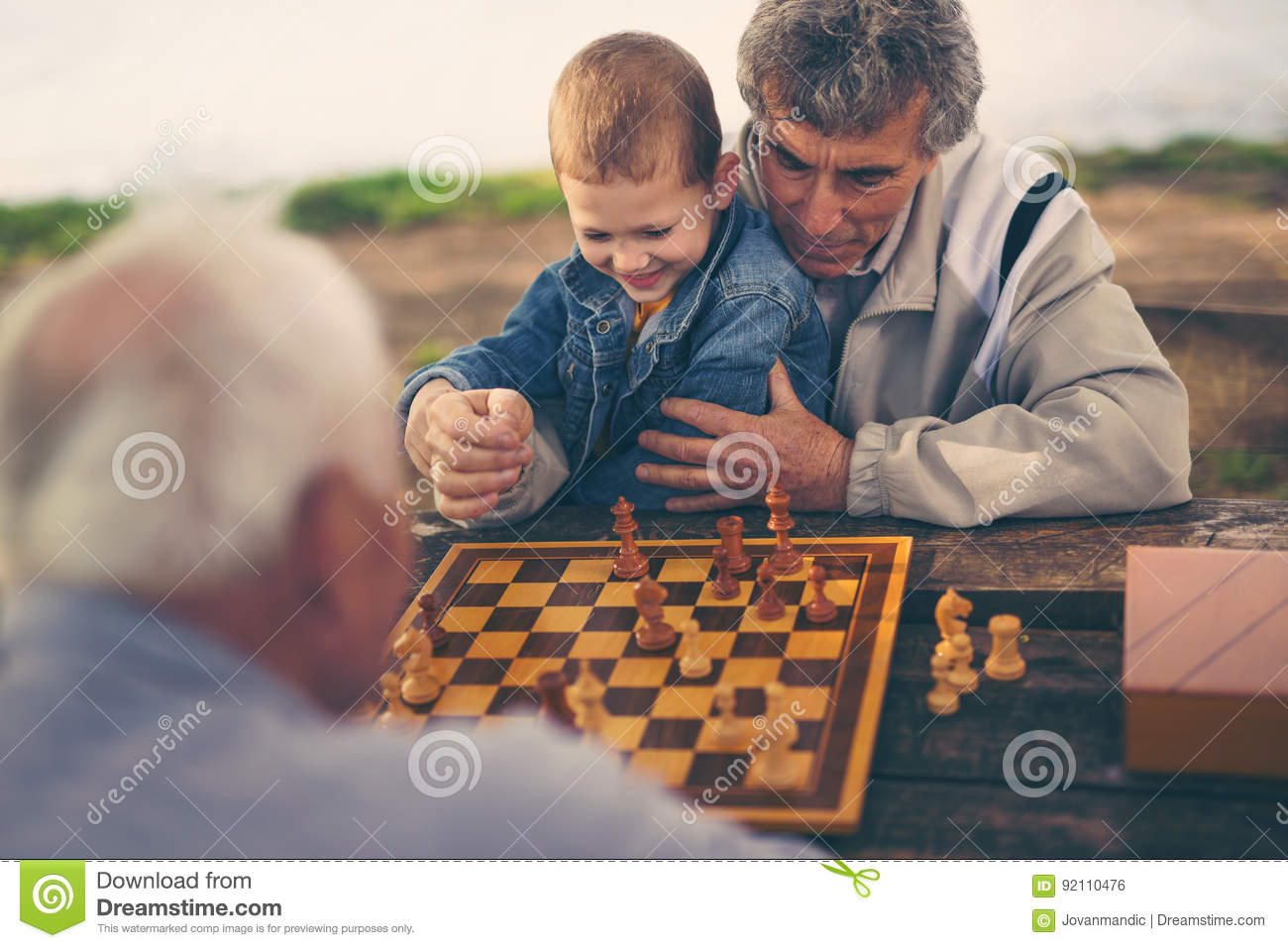 Two senior men having fun and playing chess at park