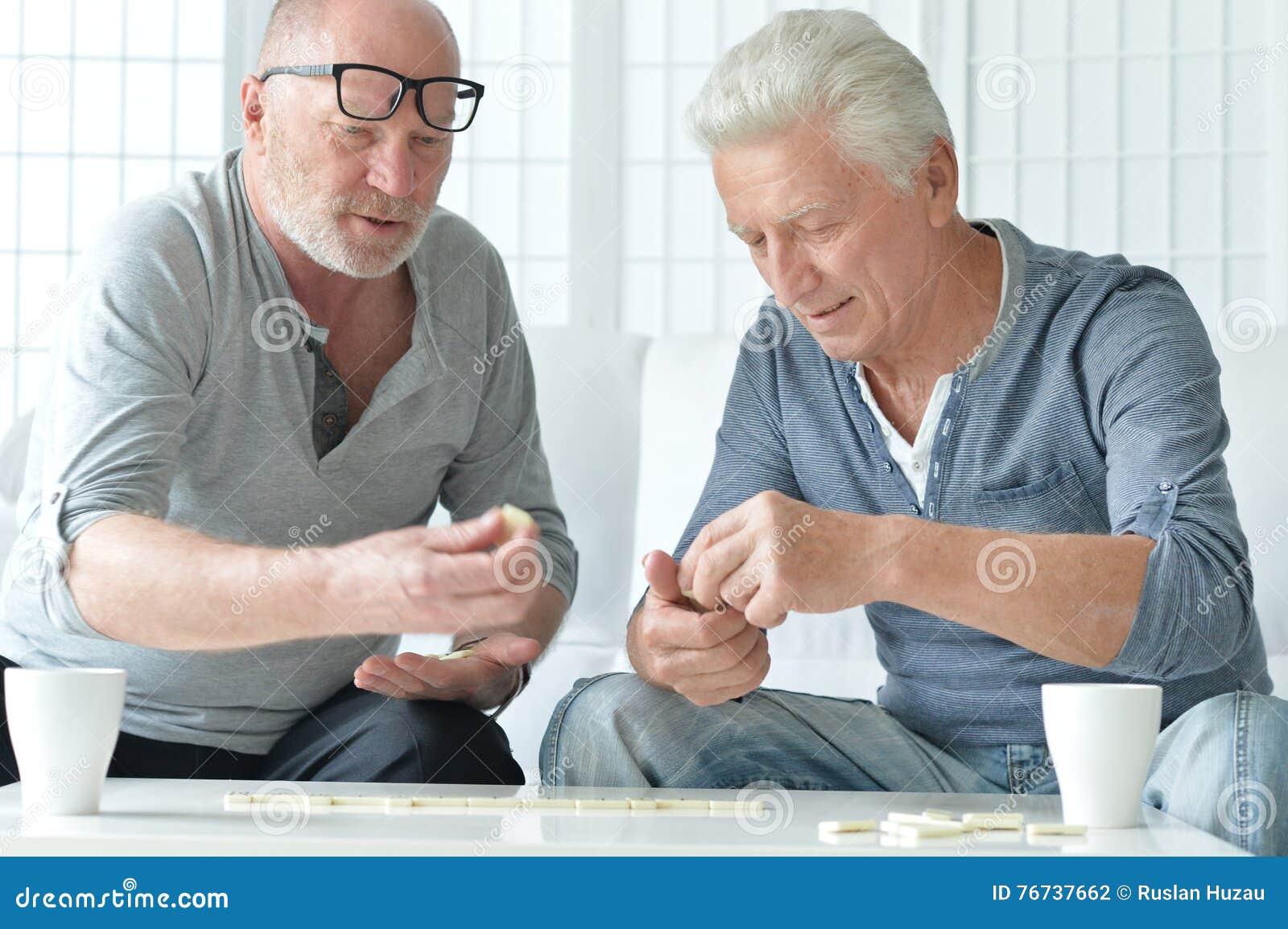 Two senior men playing domino