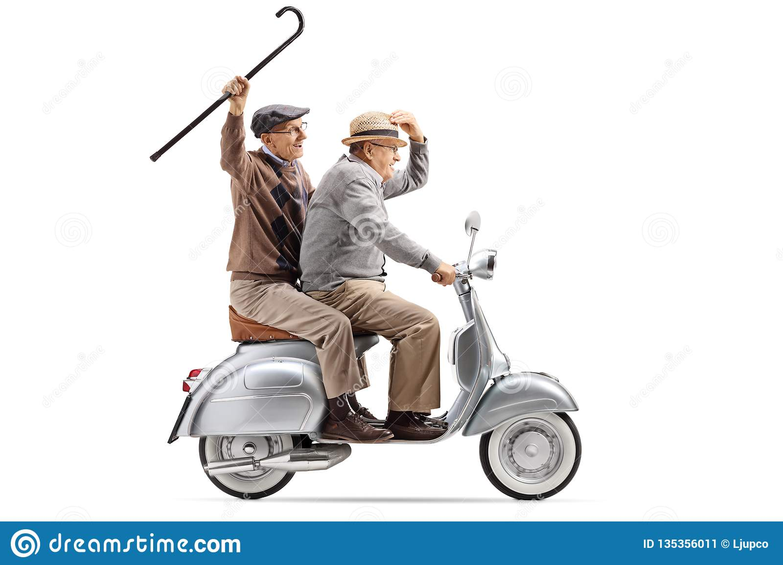 Two senior men riding a vintage scooter and waving with a cane