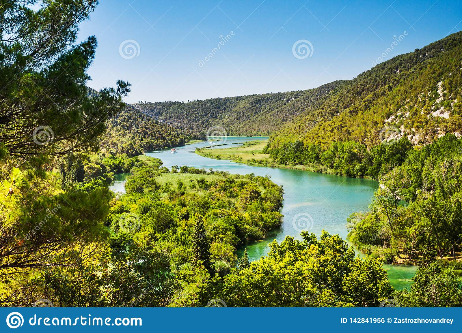 Two ships sail on the river. Around the forest and mountains. Krka, National Park, Dalmatia, Croatia
