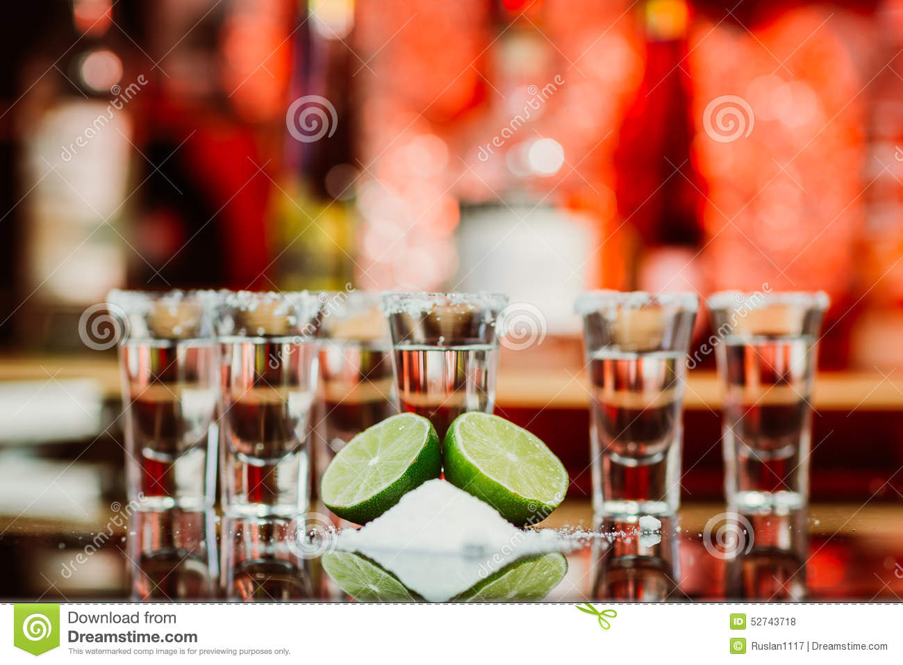 Two shots of tequila with lime and salt on a wooden table bar on the background of bright lights of the bar