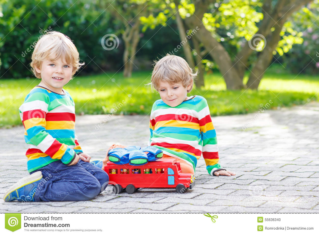 Toys For Siblings : Two siblings kid boys playing with red school bus stock