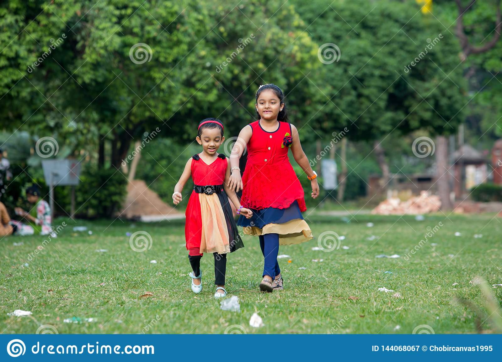 Two sister play with red dress in ground