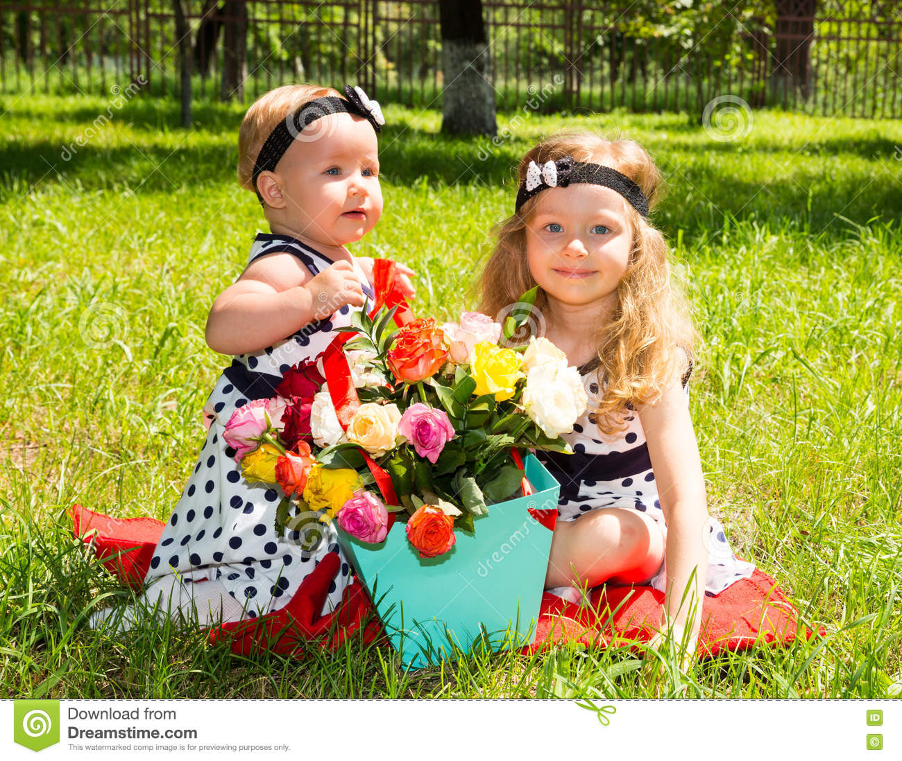 Two sisters. Adorable little child girls with bouquet of flowers on happy birthday.