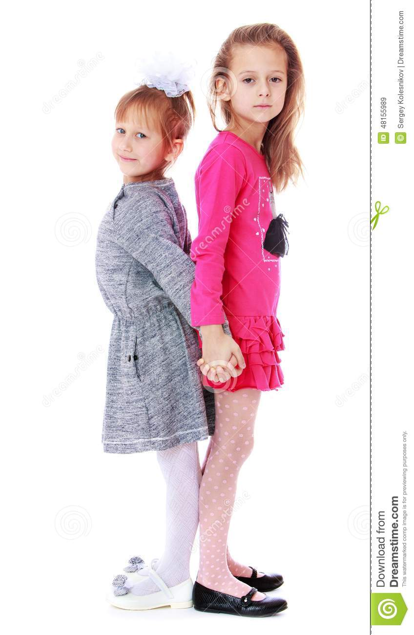 Two girls standing back to back holding hands.Studio photo, isolated ...