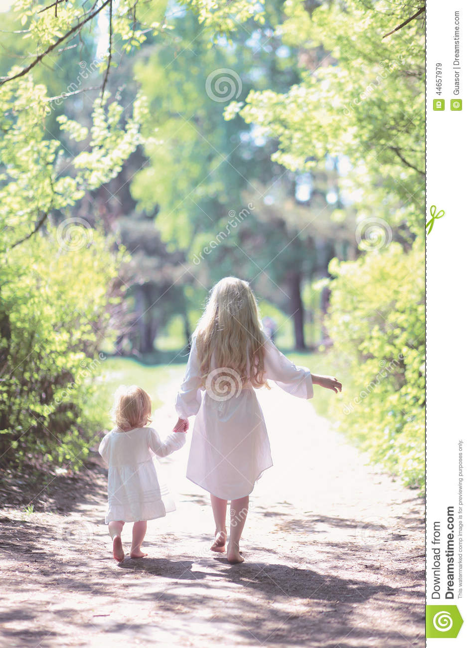 Two sisters holding hands walking in the forest on a summer day Two Sisters Holding Hands