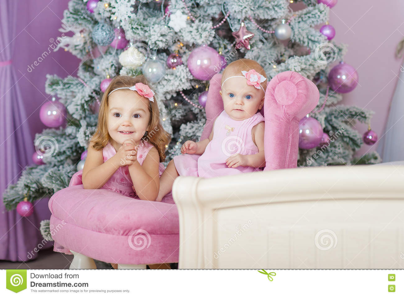 Two sisters at home with Christmas tree. Portrait of happy children girls decorations.