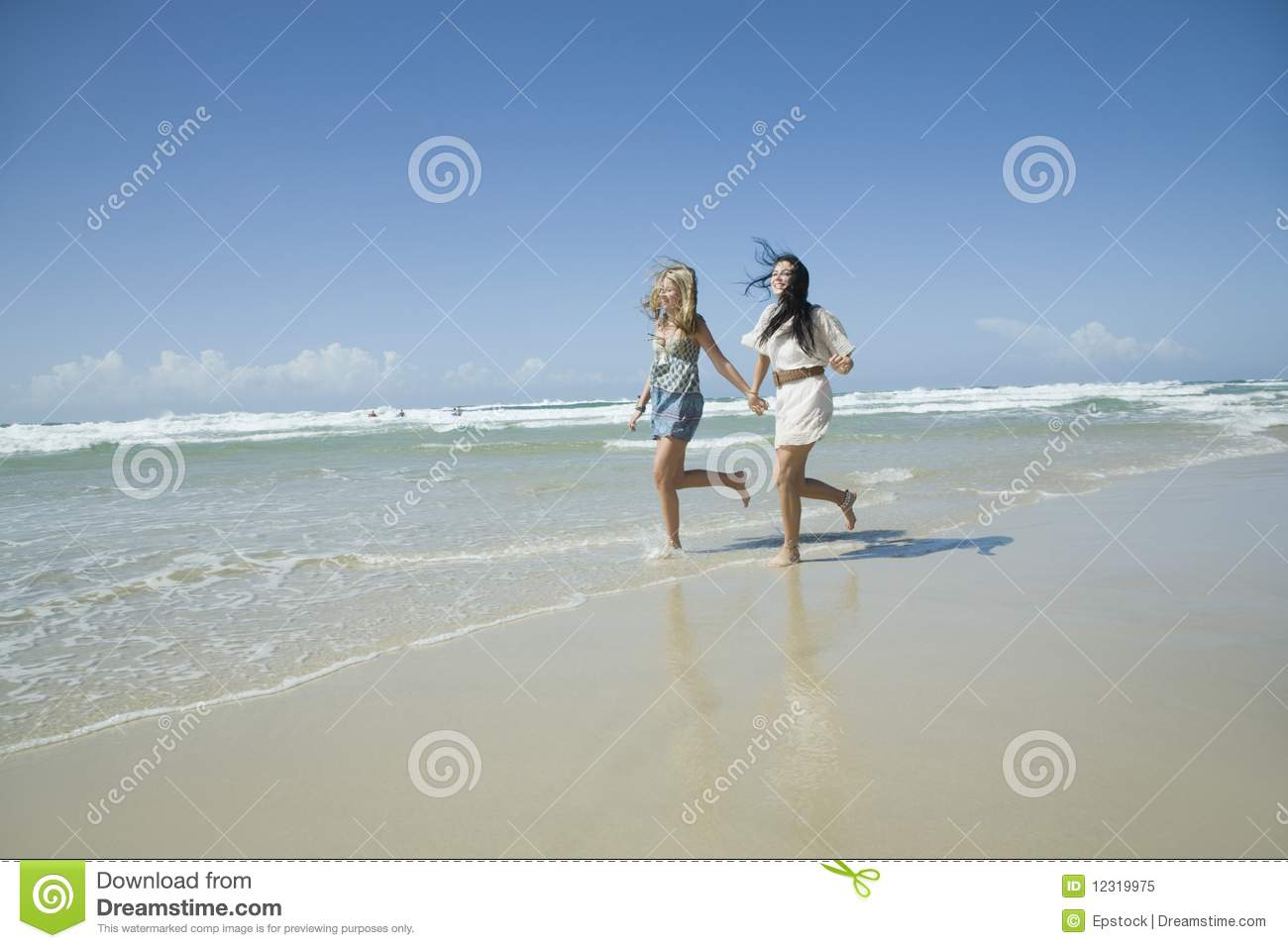 Royalty Free Stock Photo  Two sisters running on beach holding handsTwo Sisters Holding Hands