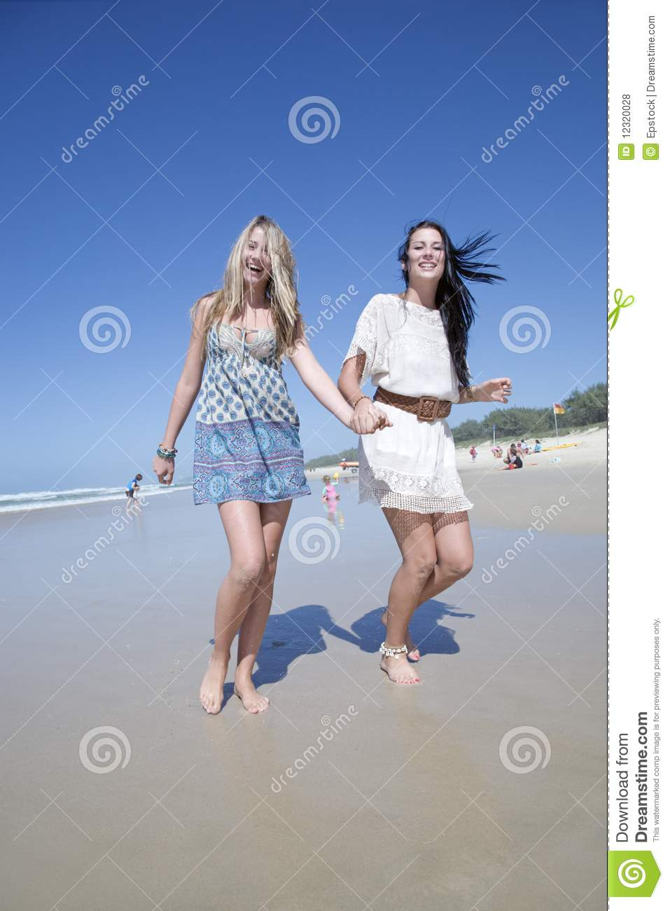 Two sisters running and laughing on beach holding hands Two Sisters Holding Hands