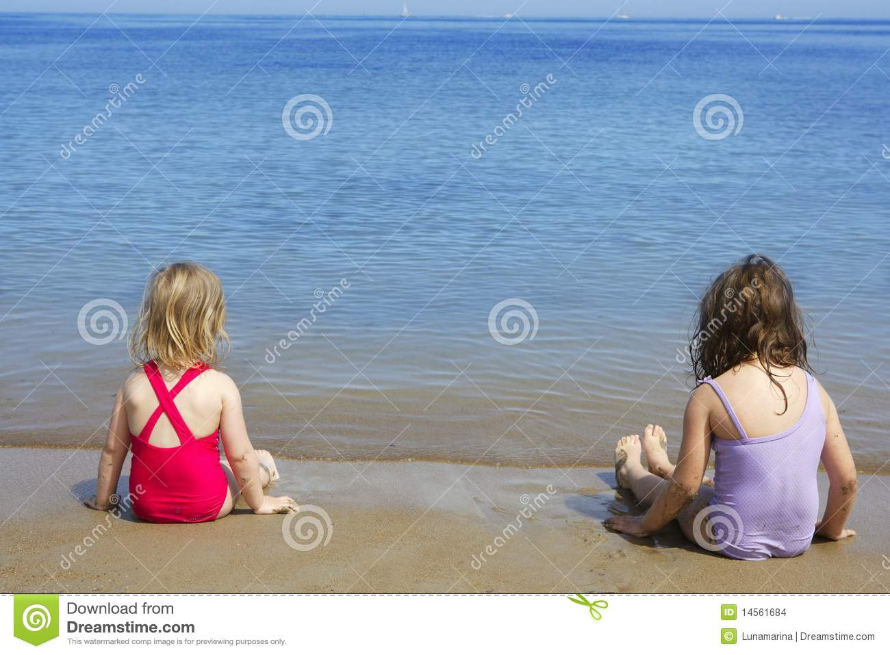Two sisters sit on beach bathing suit swimsuit