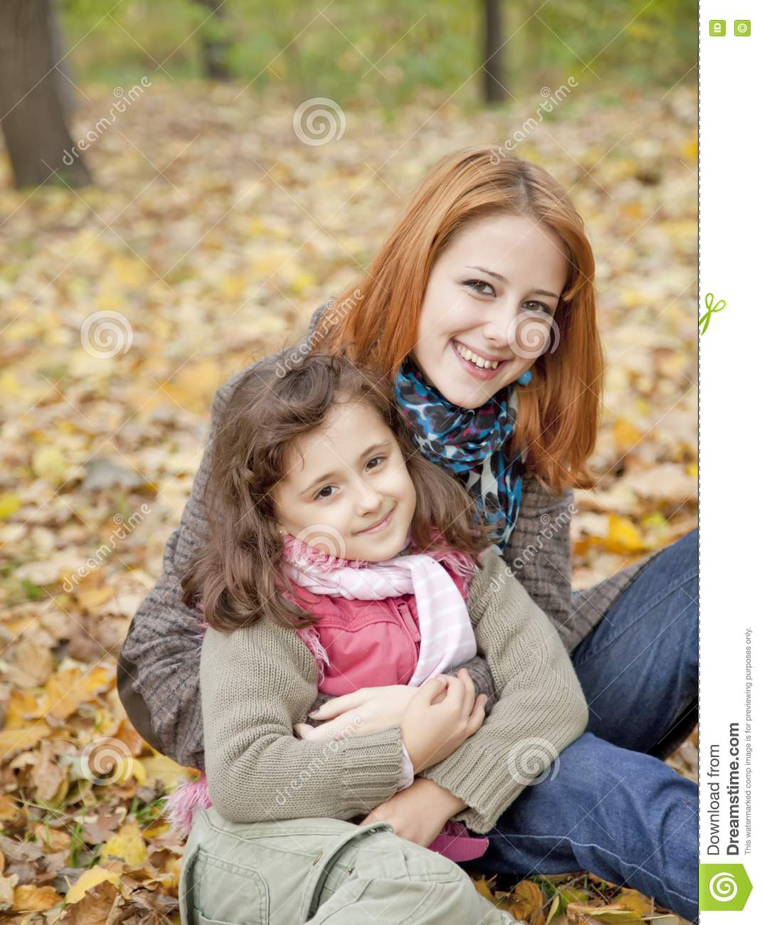 Two Sisters Sitting On The Leafs In The Park. Royalty Free Stock ...