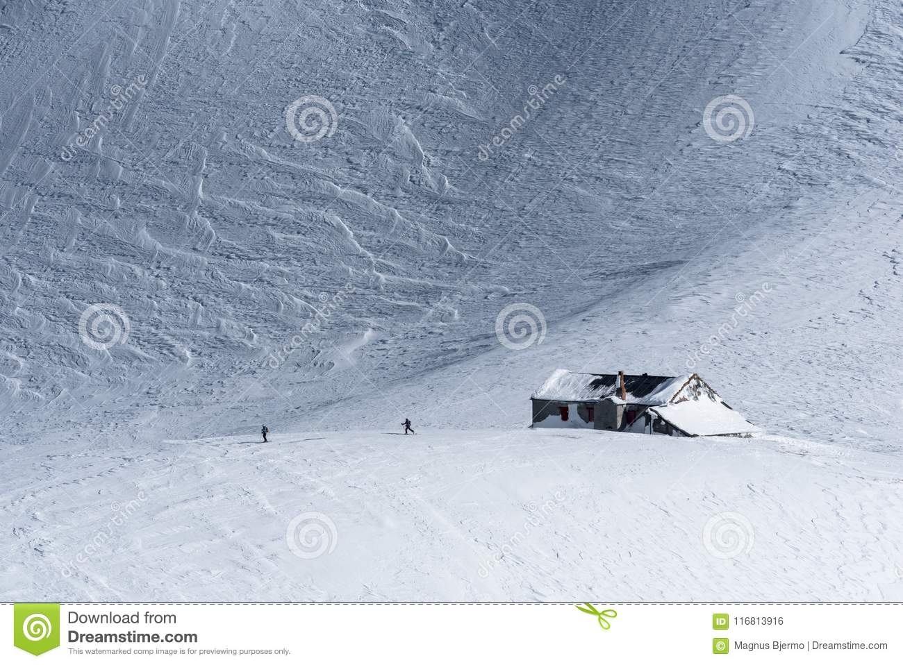 Snow covered alpine mountain hut with two skiers in winter