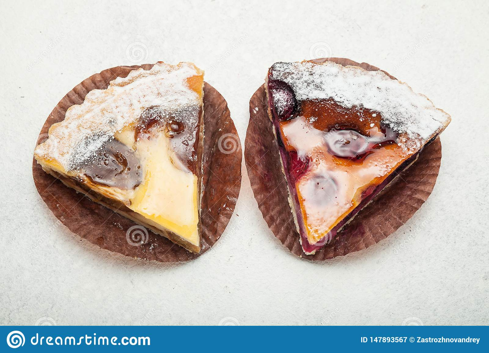 Two slices of fruit pies on a white vintage background