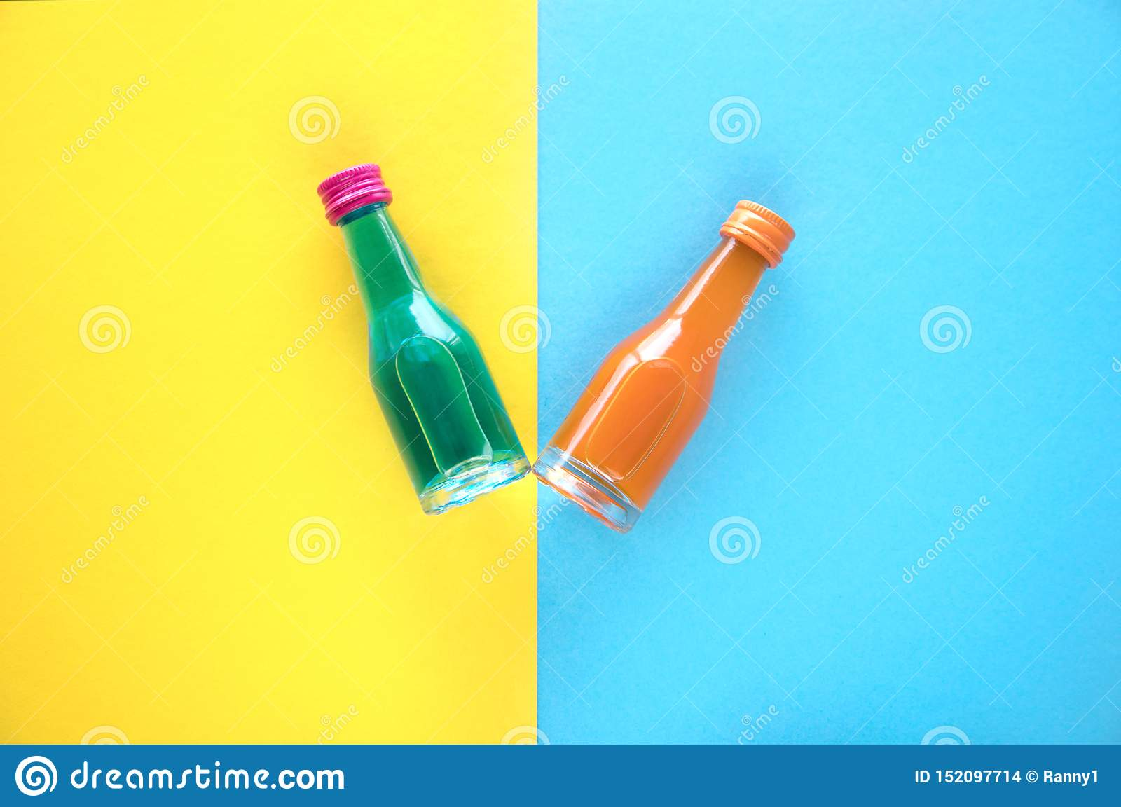 Two small glass bottles with a blue and orange cocktail on a blue and yellow background. Two multi-colored small bottles with