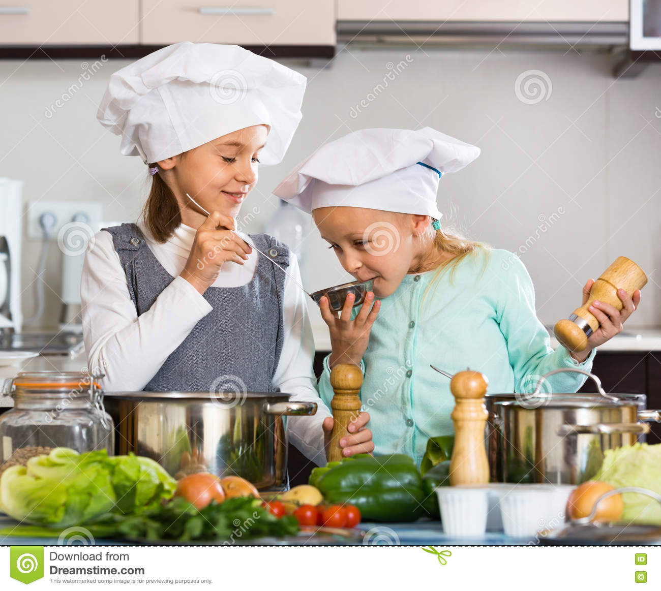 Two Small Happy Girls Cooking Vegetable Soup Stock Photo