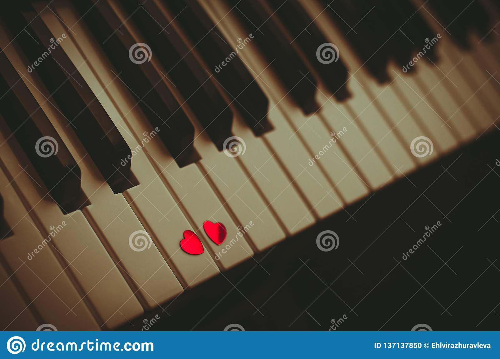 Two Small Red Hearts On The Keyboard Of Classic Piano Close