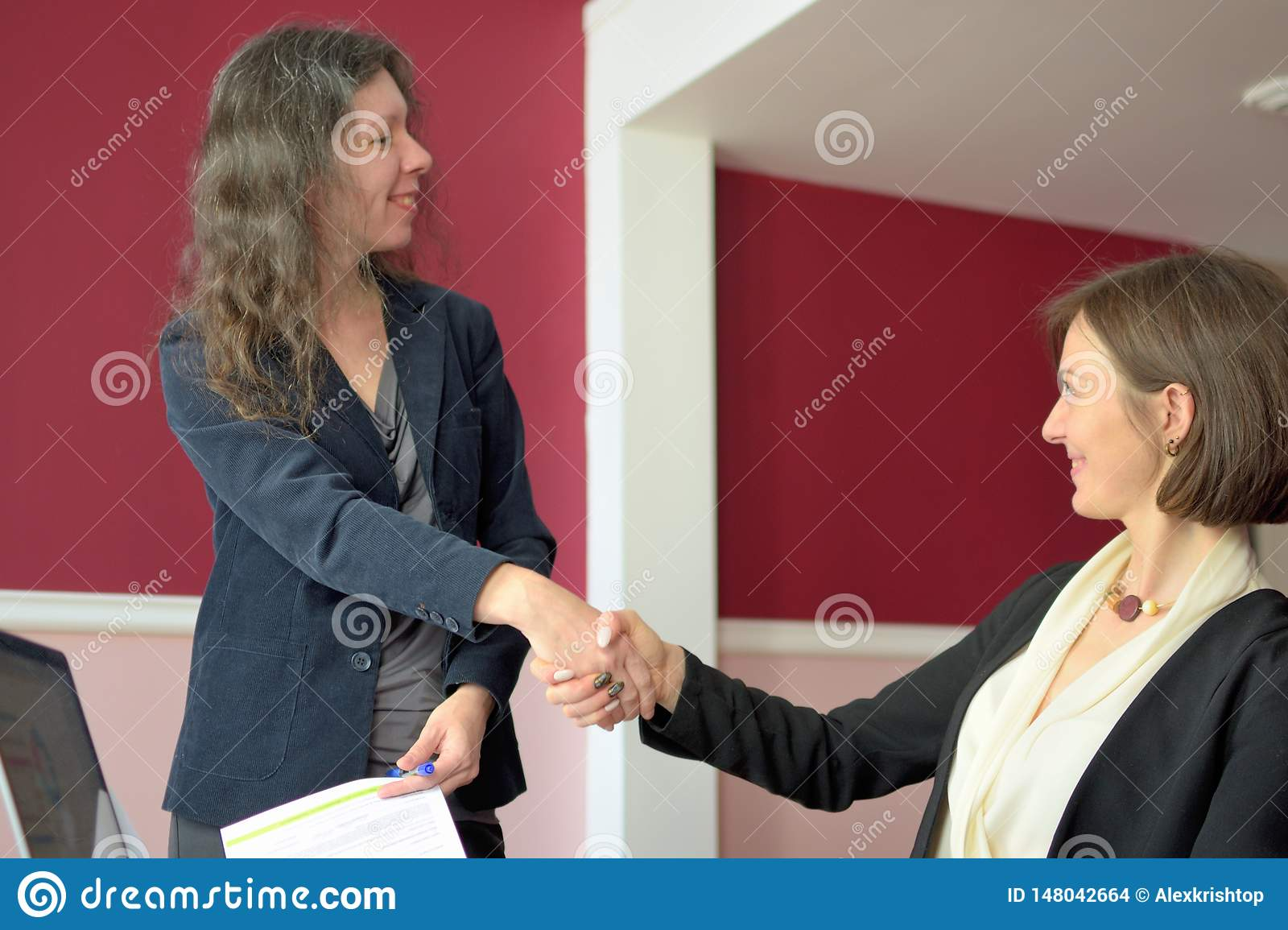 Young smartly dressed lady helps another young lady to work with documents, fill forms and sign