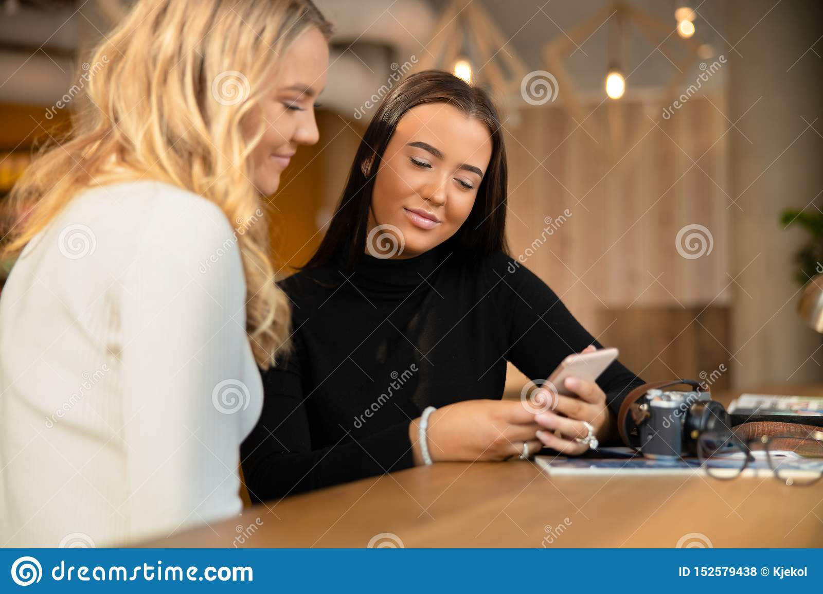 Two Smiling and Beautiful Young Friends Looking At Smartphone In Cafe