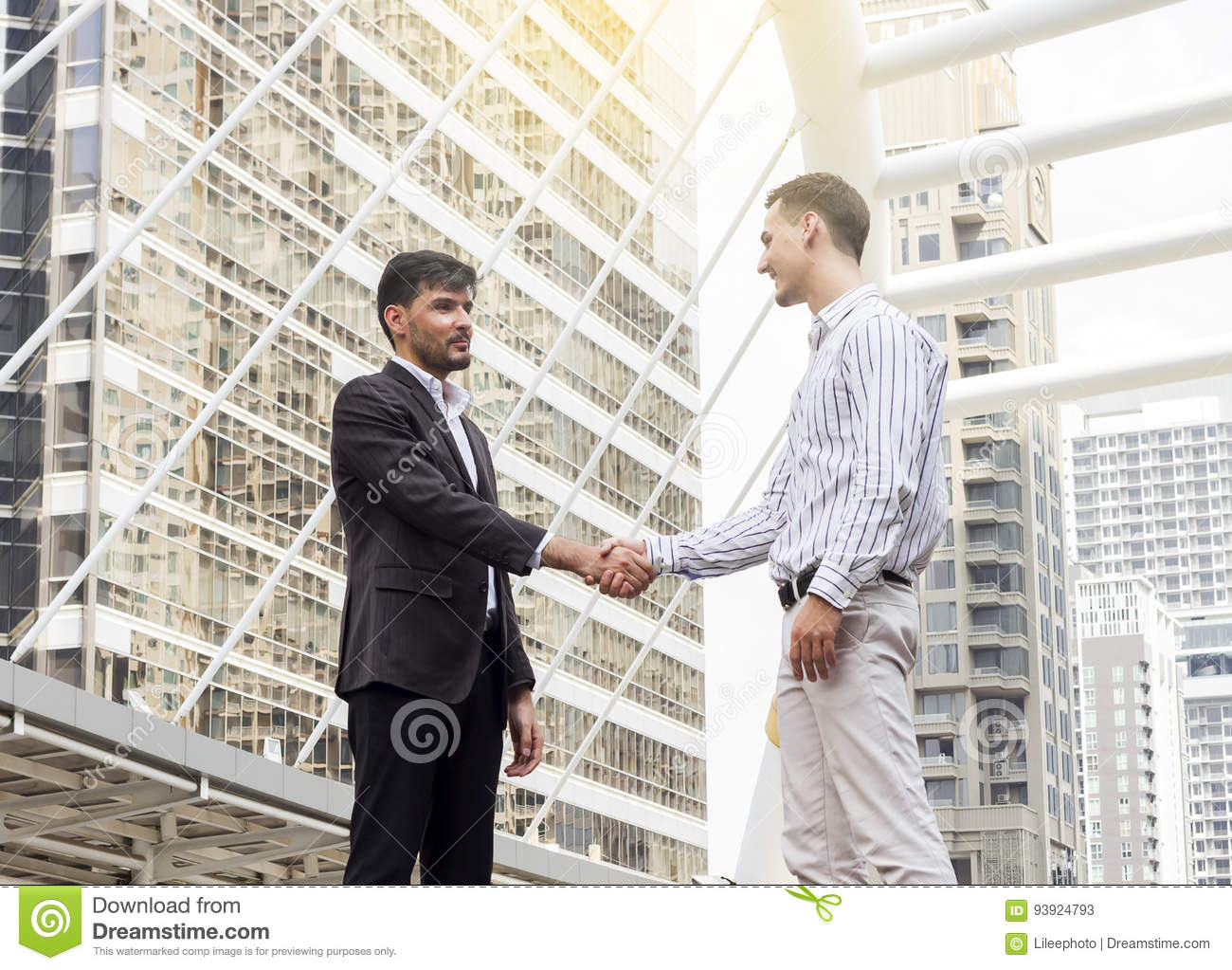 Two smiling businessmen shaking hands together.