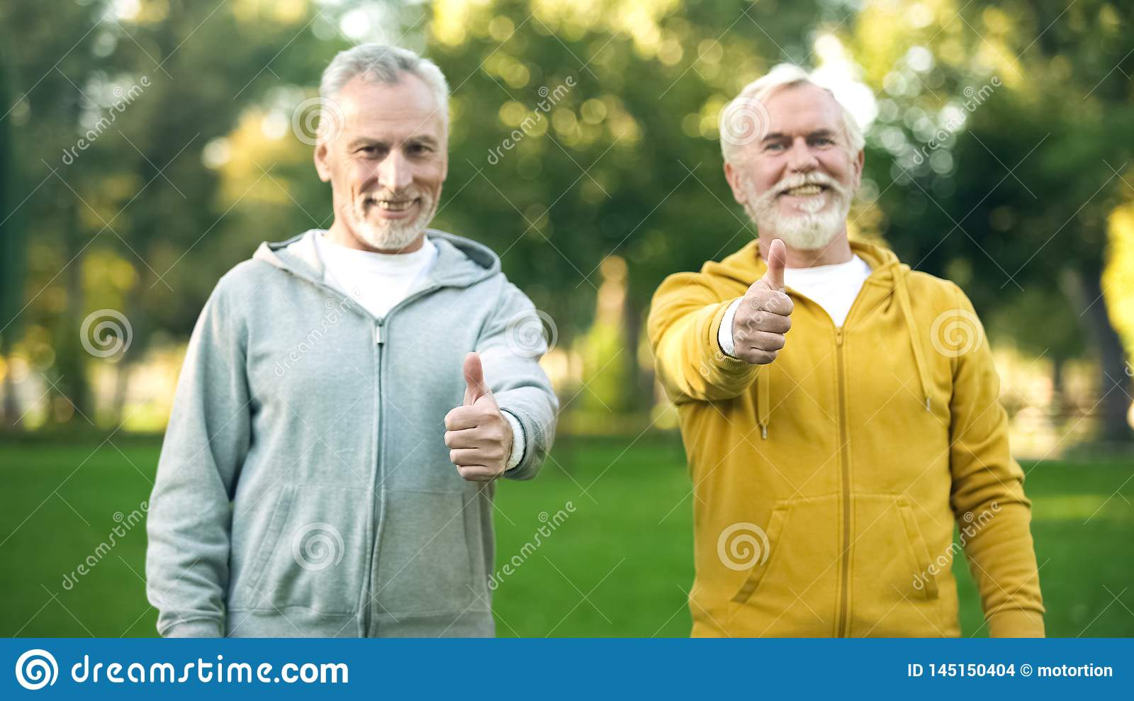 Two smiling elderly men in sportswear showing thumbs up, healthy lifestyle