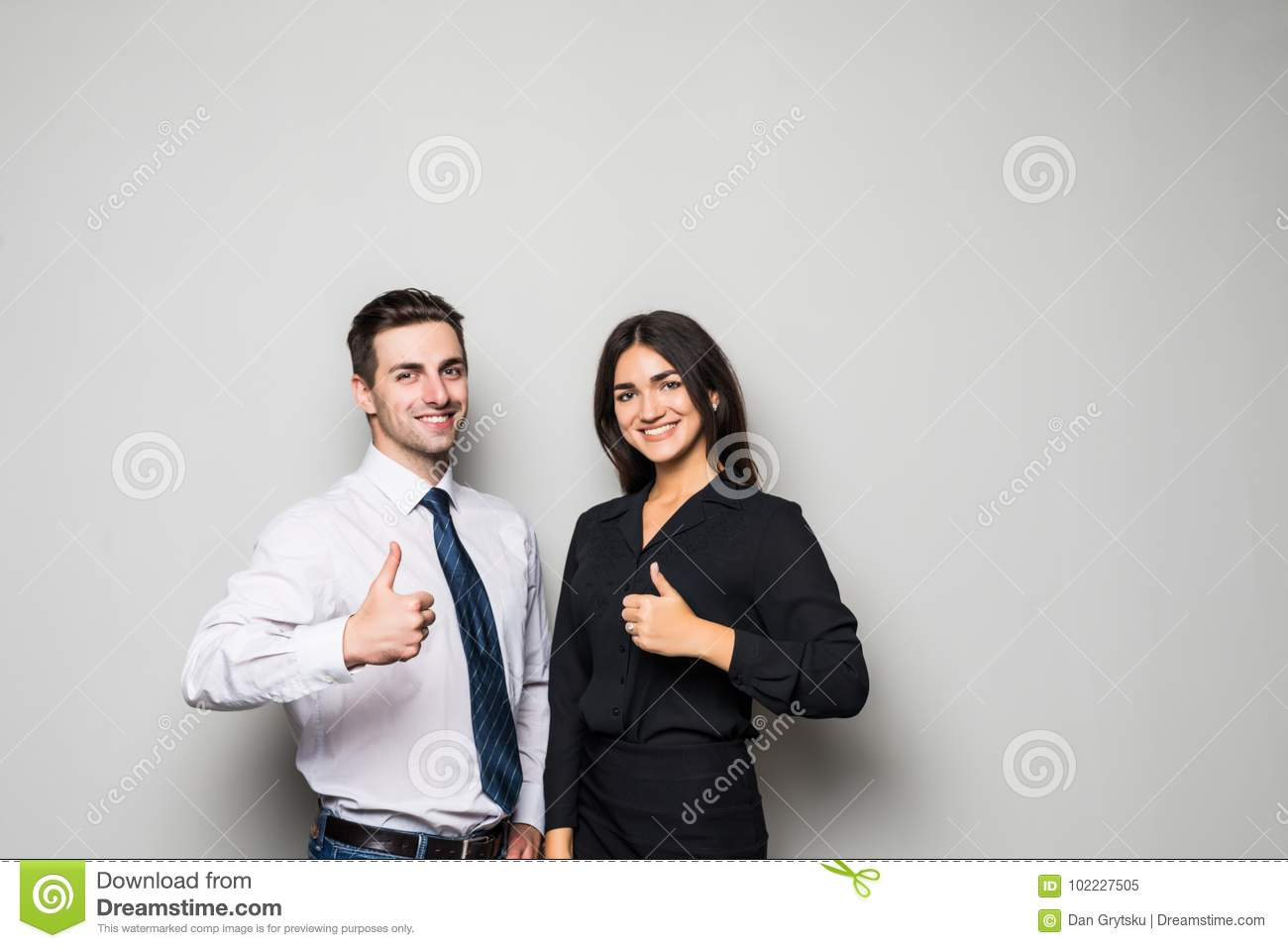 Two smiling happy businesspeople in formalwear showing thumbs-up on gray