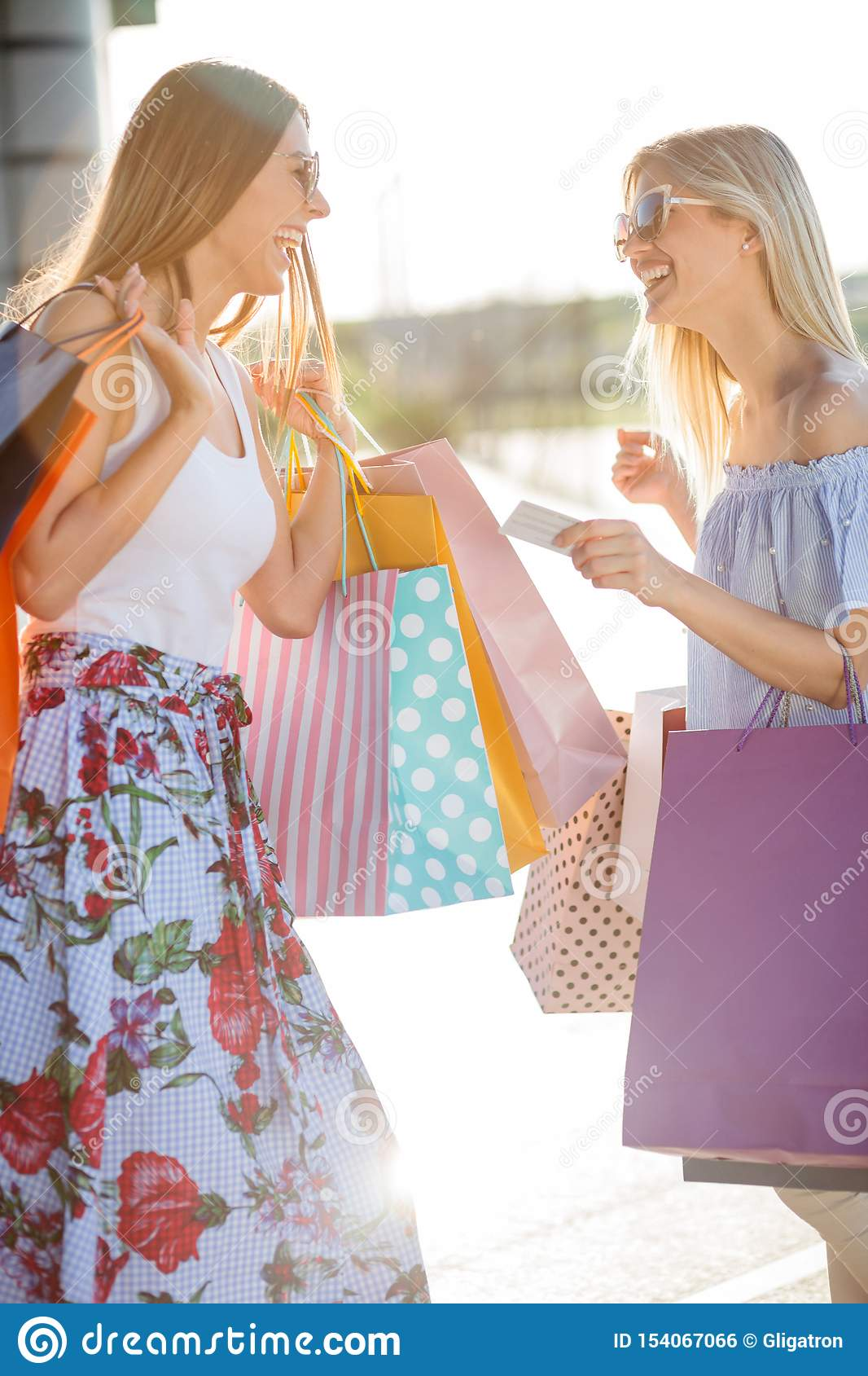 Two smiling happy young women returning from shopping
