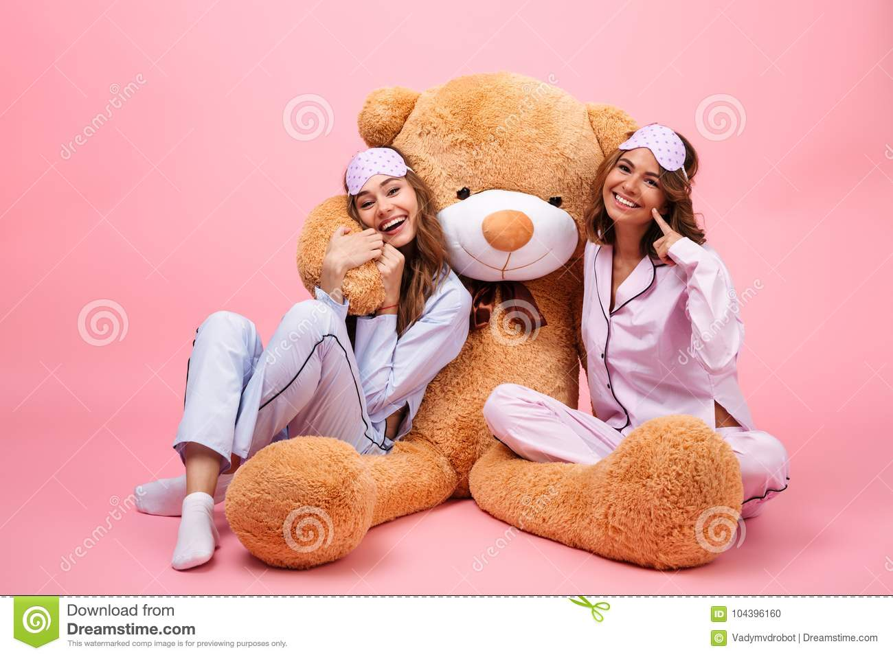 Two smiling pretty girls dressed in pajamas sitting with a big teddy bear  and hugging isolated over pink ed3318678