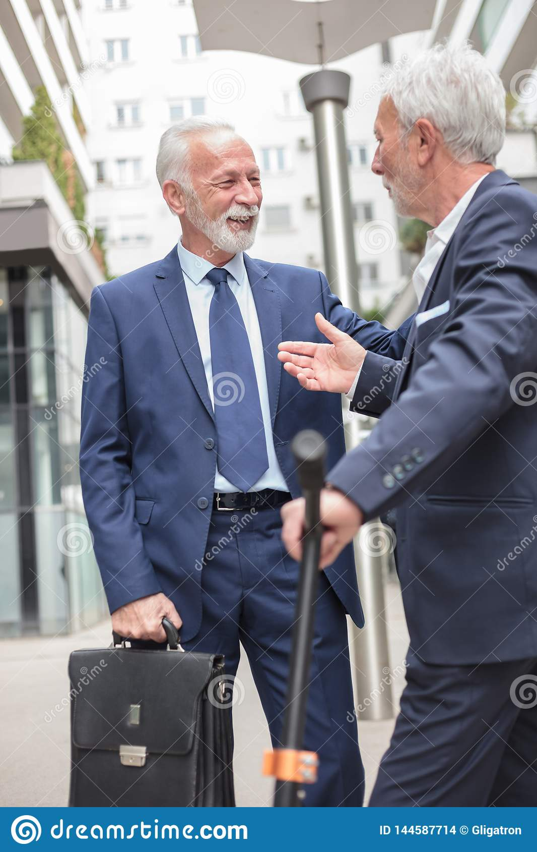 Two smiling senior businessmen meeting and talking on the sidewalk, surrounded by office buildings