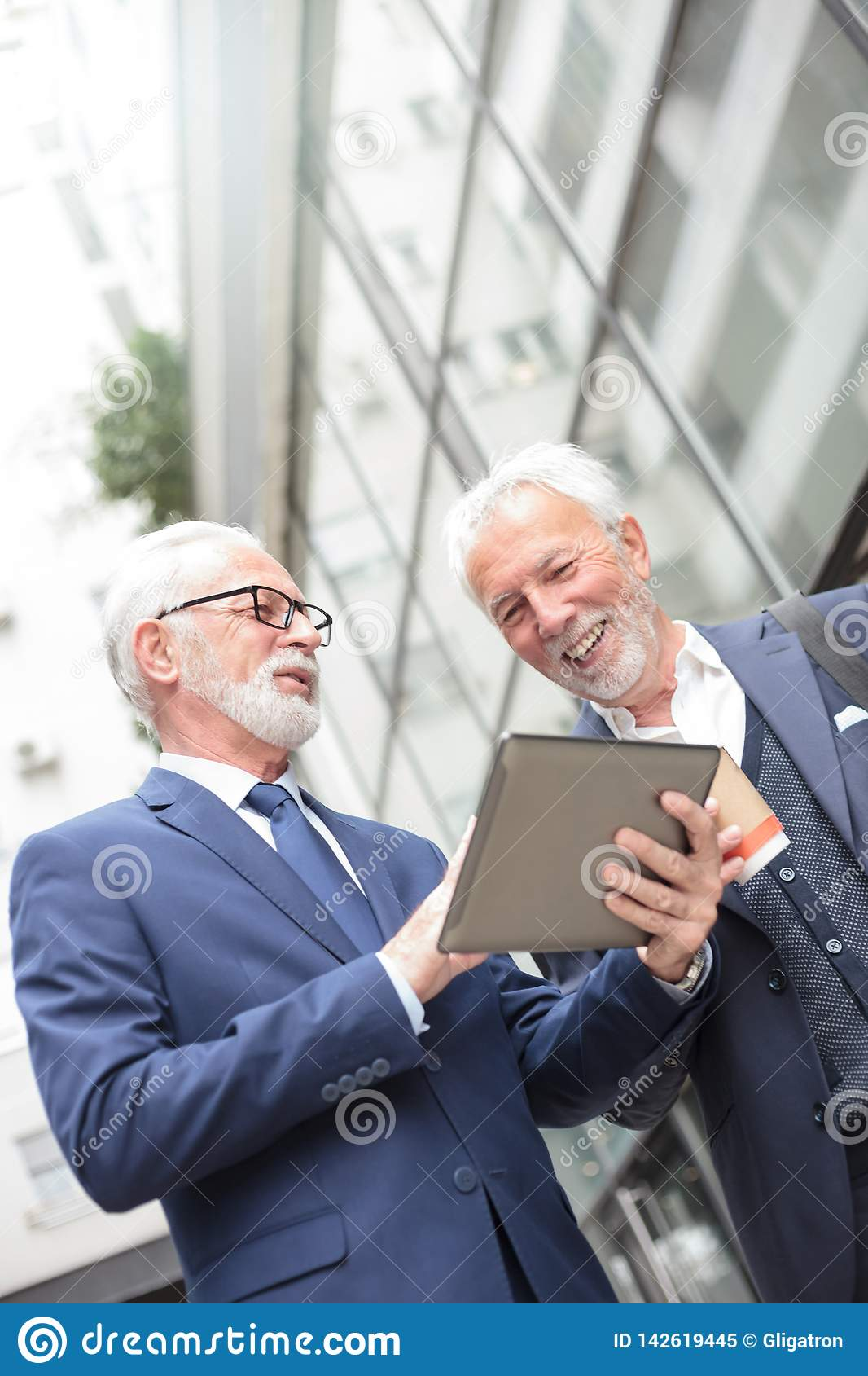 Two smiling senior businessmen working on a tablet standing in front of an office building