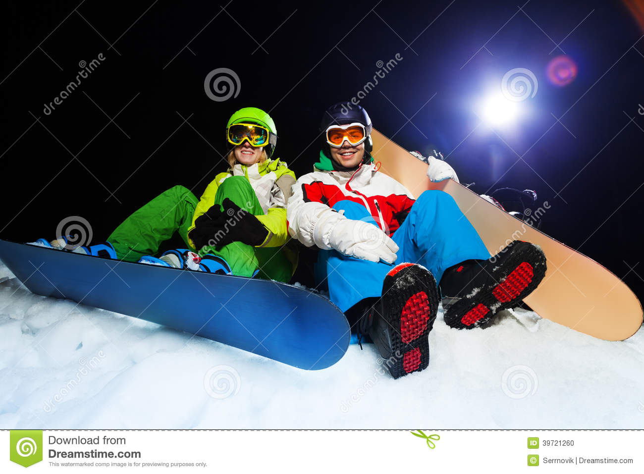 d167638bb9b5 Two smiling snowboarders wearing ski masks sitting together at night with  flash on the background
