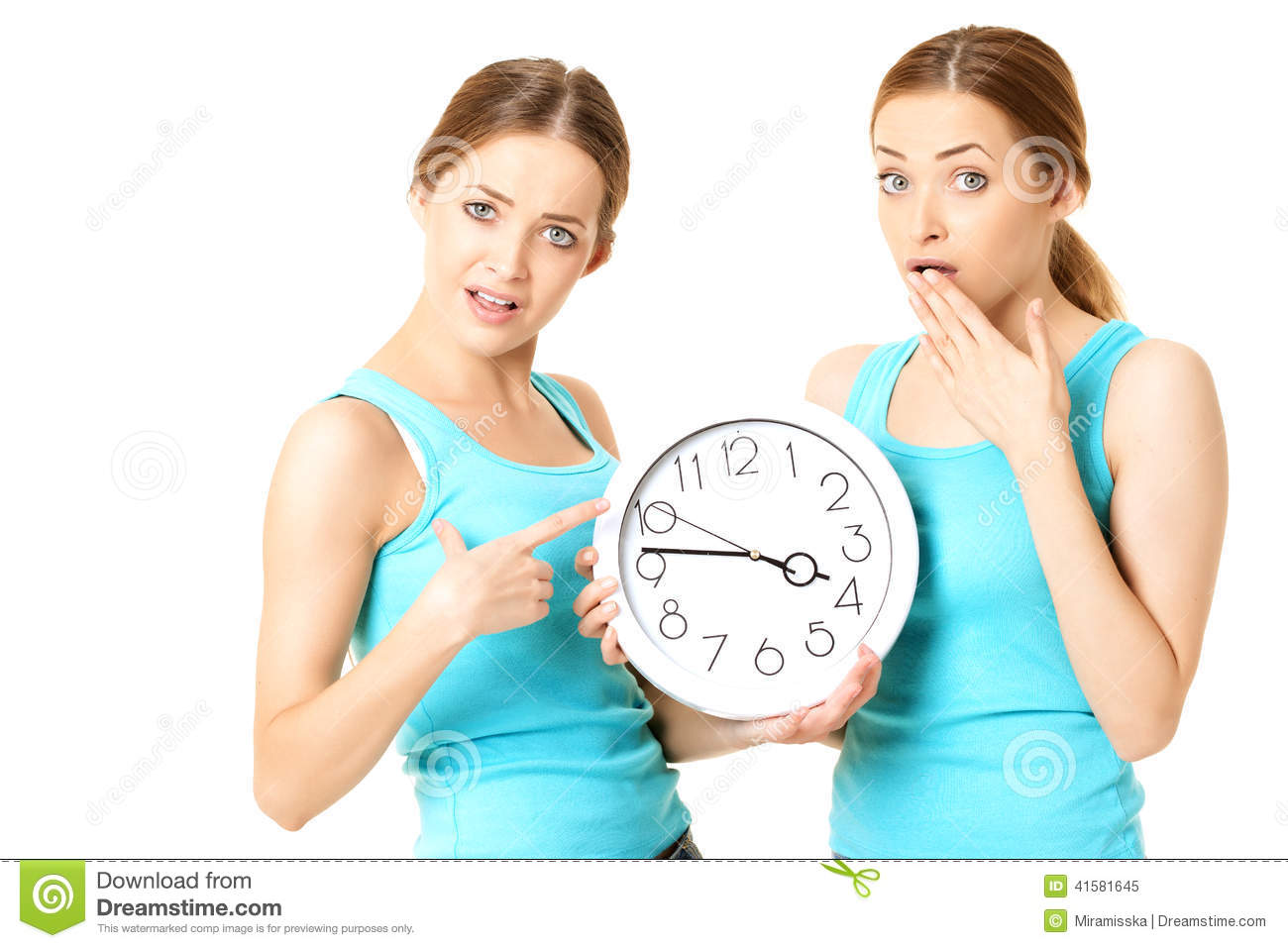 Two smiling women holding a clock