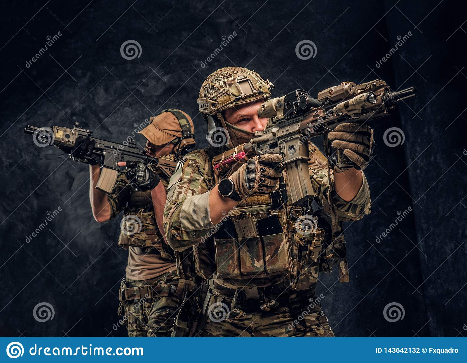 Two special forces soldiers in full protective equipment holding assault rifles and aiming at the targets. Studio photo