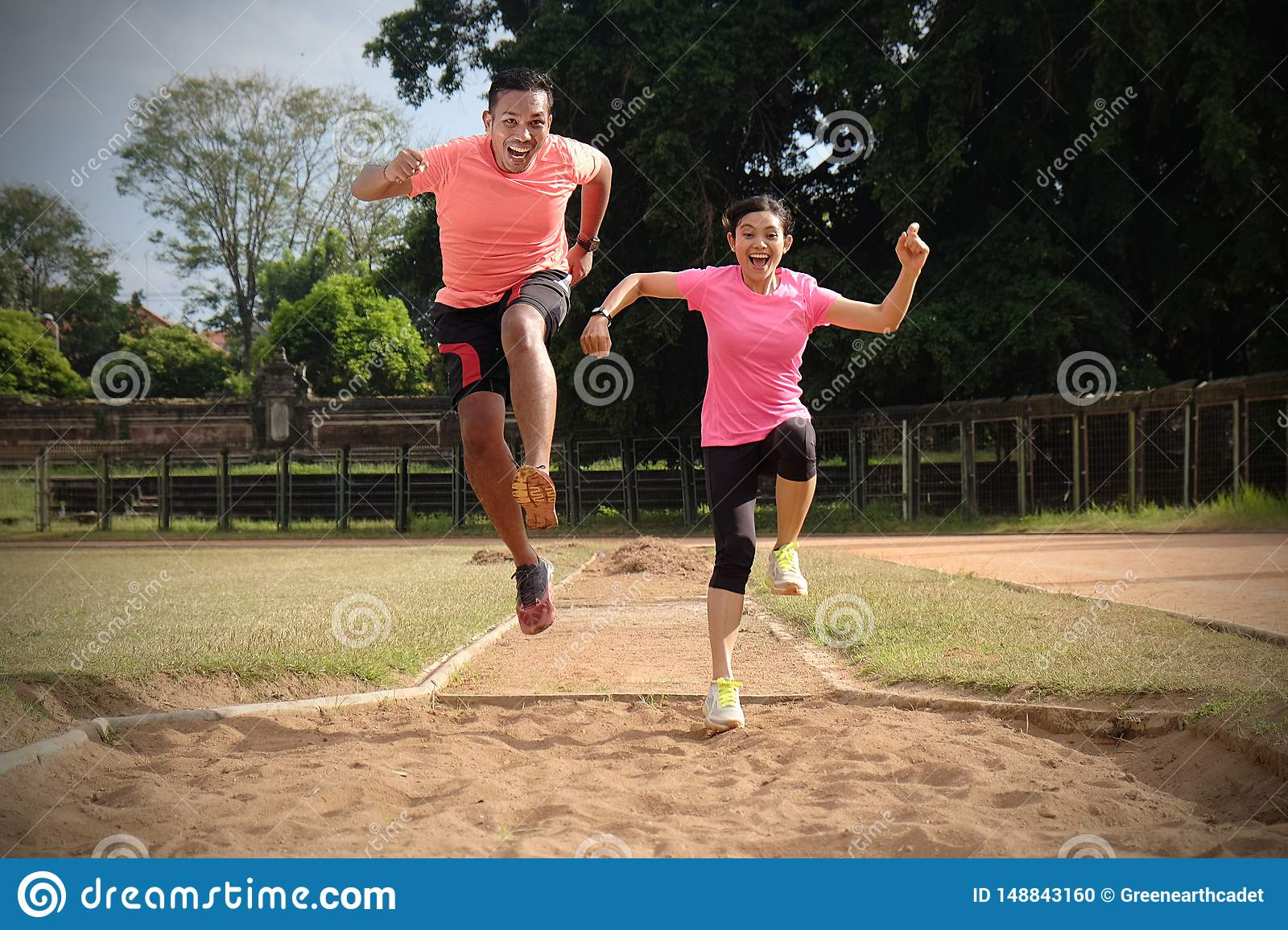 Two sports partners are jogging together on a sunny day wearing orange and pink shirts. They look at each other and smile, enjoy