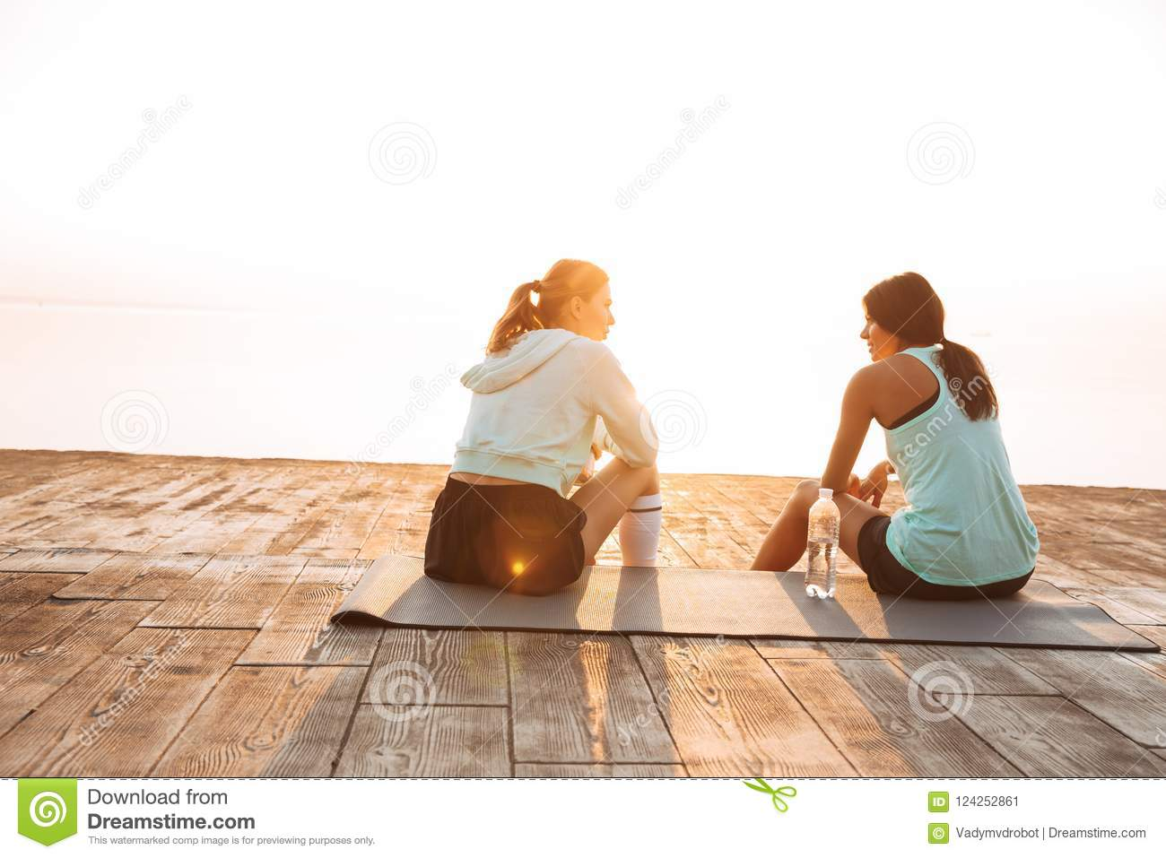 Two sports women friends outdoors on the beach sitting talking with each other