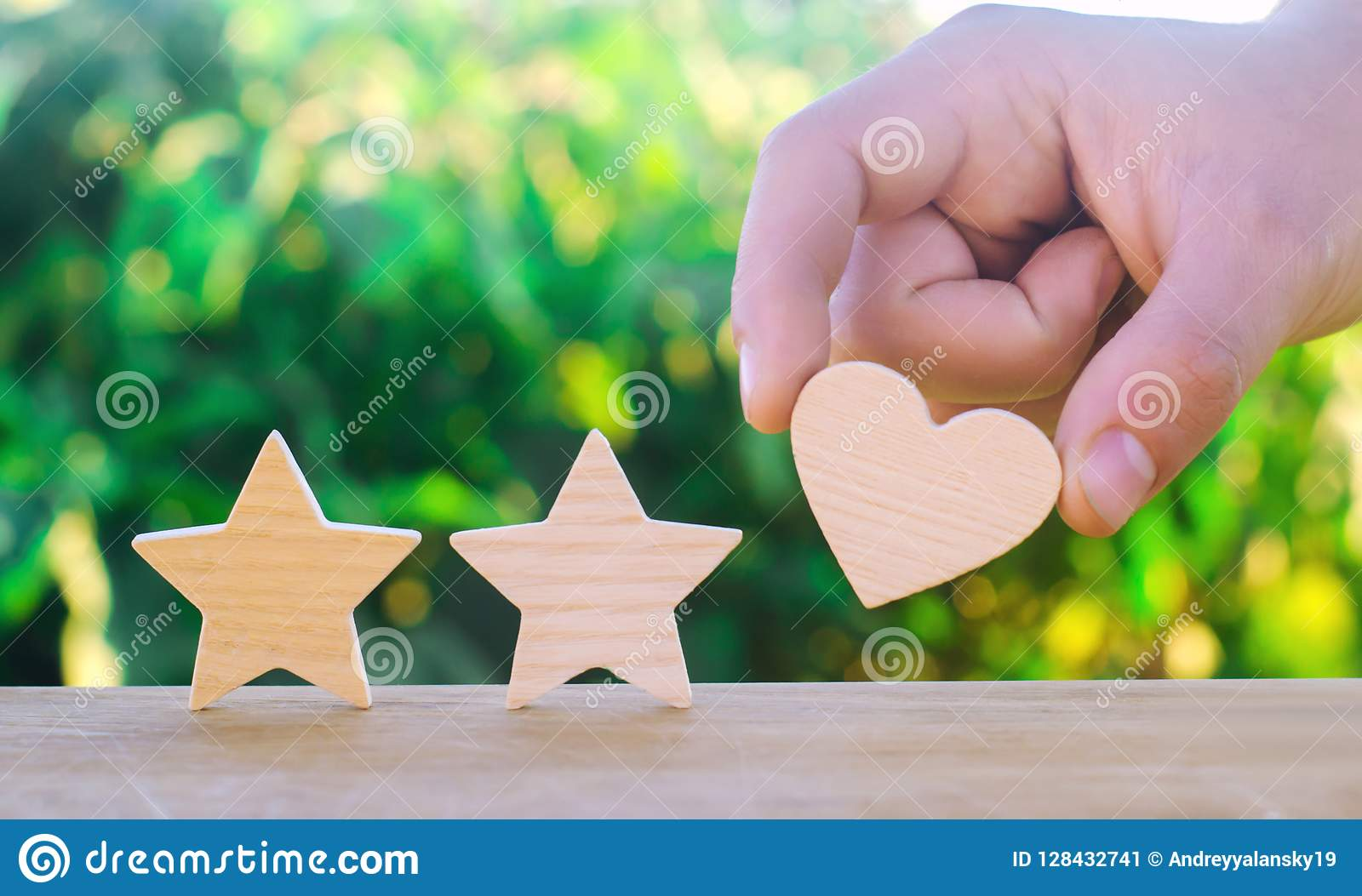 Two stars and heart on a green bokeh background. three star rating, the choice of the editorial office and the buyer. concept of r