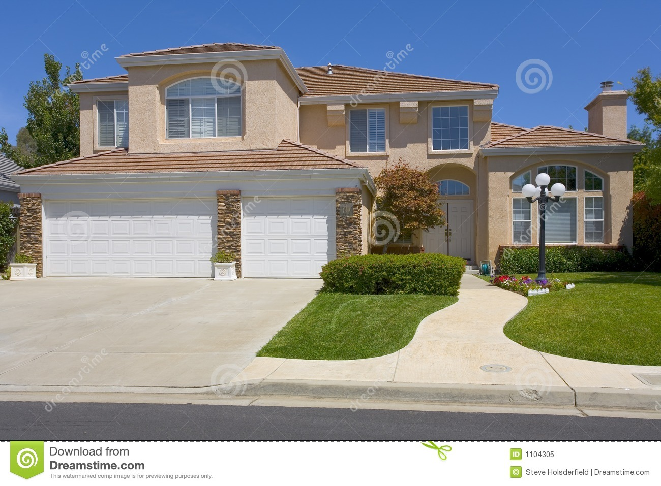 Two story stucco home with a street light stock image for A 2 story house