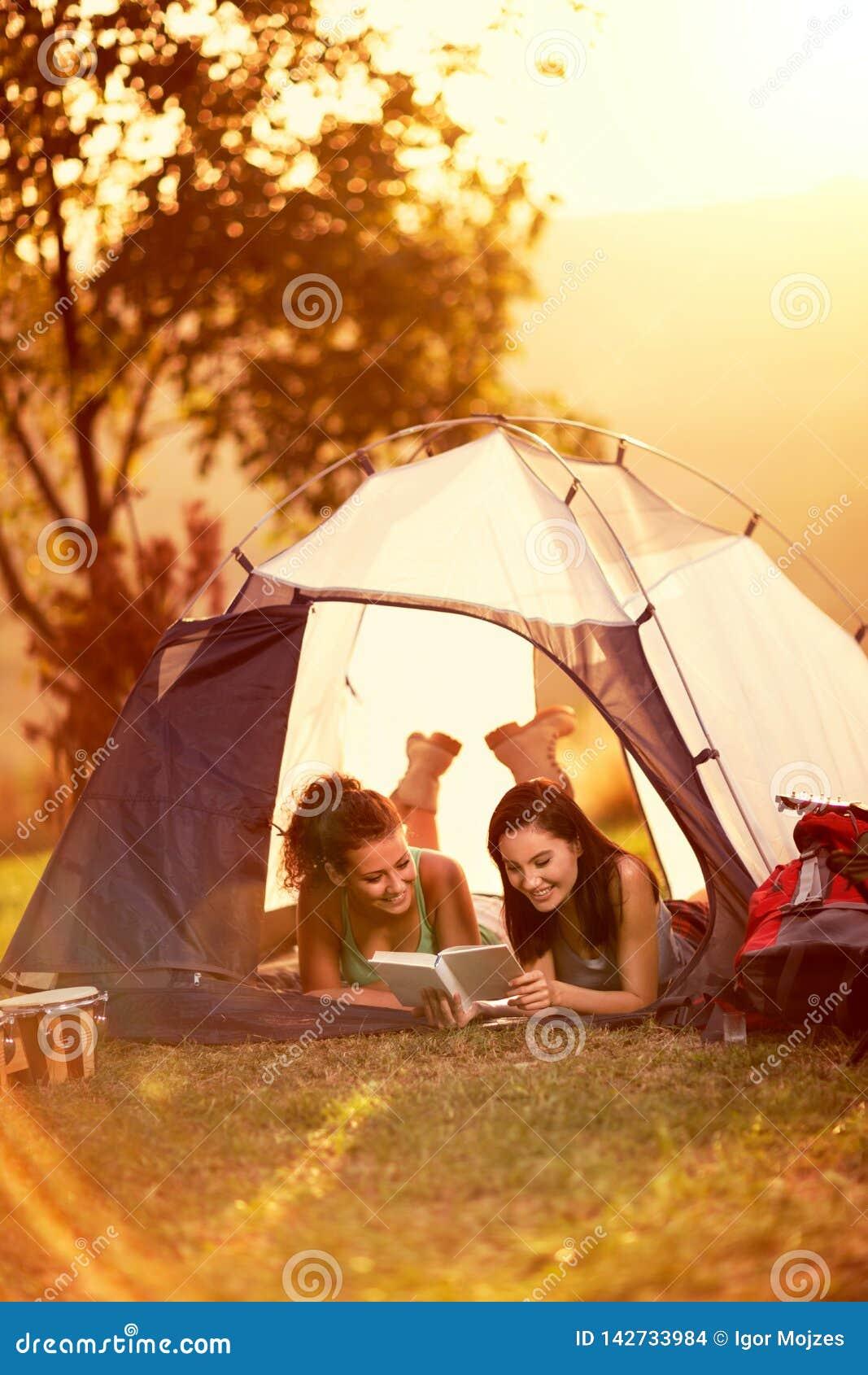 Two girlfriends enjoying in camping trip