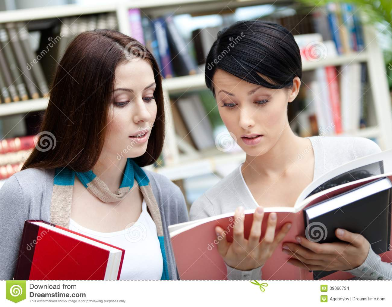 Two students with books at the library