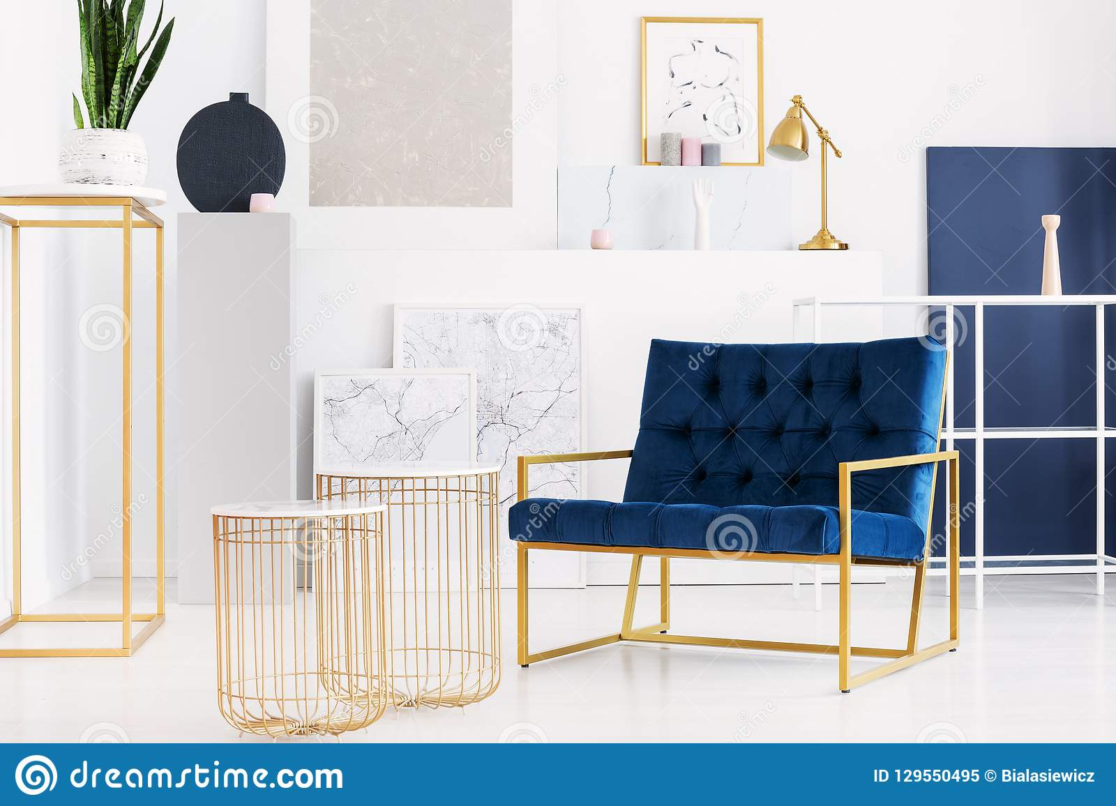 Two stylish tables next to petrol blue armchair in bright living room interior of modern apartment