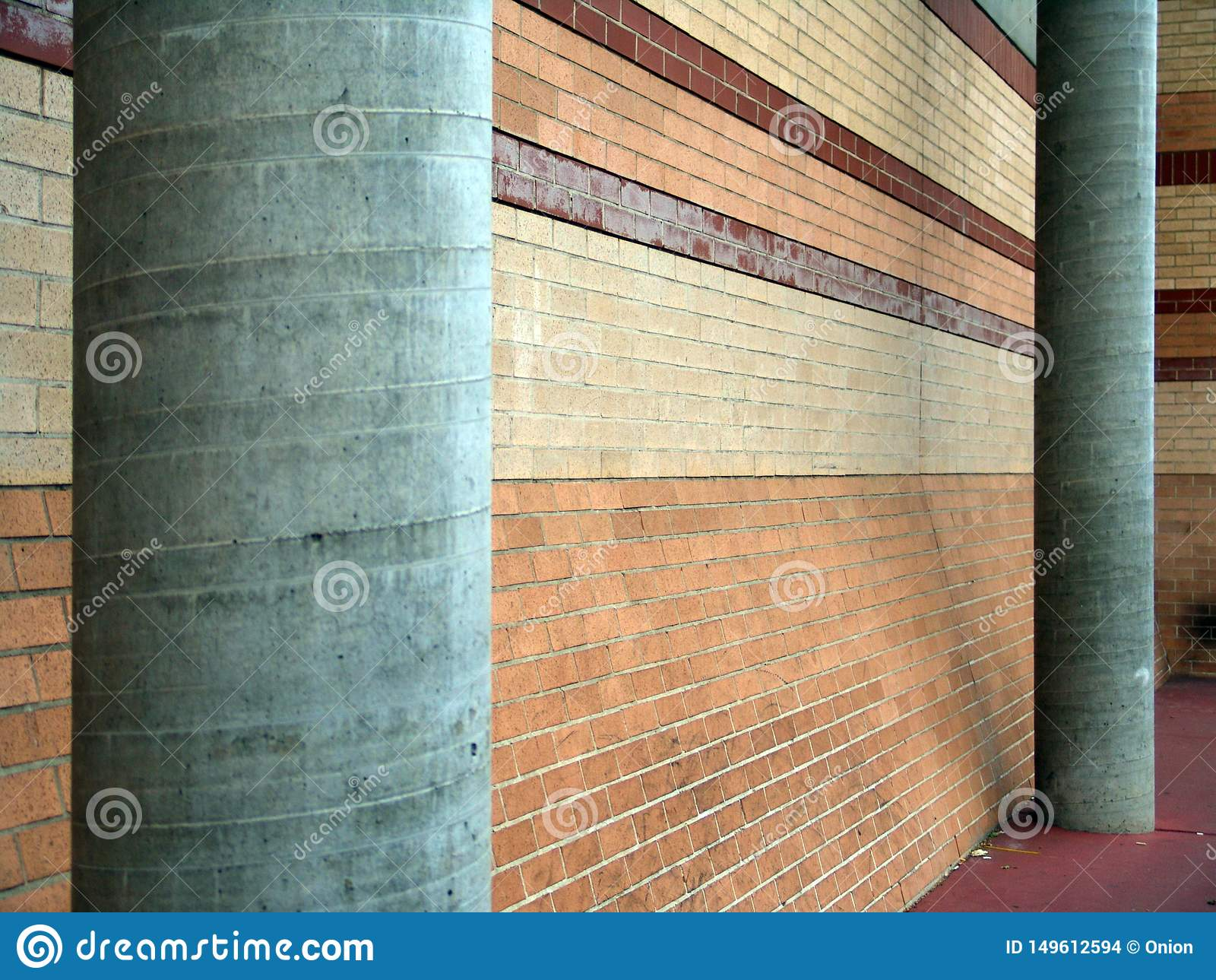 Two support pillars in grey next to a brick wall