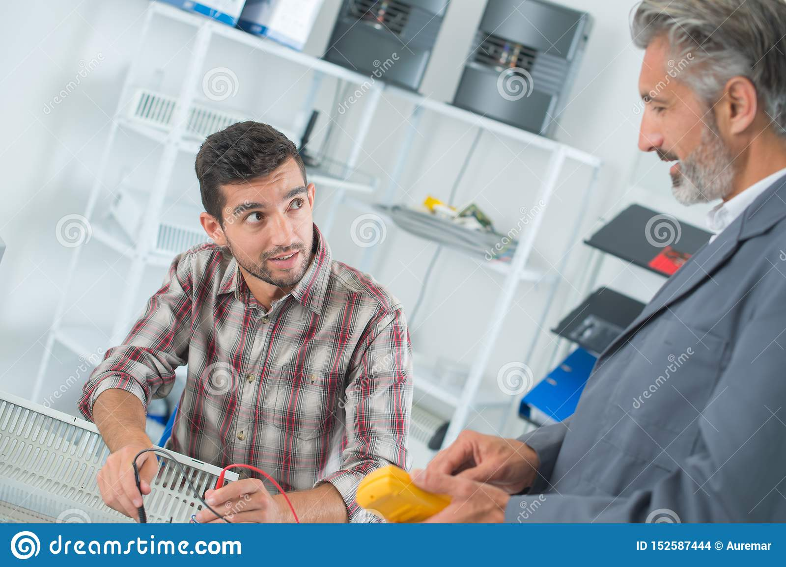 Two technicians using multimeter on electrical appliance